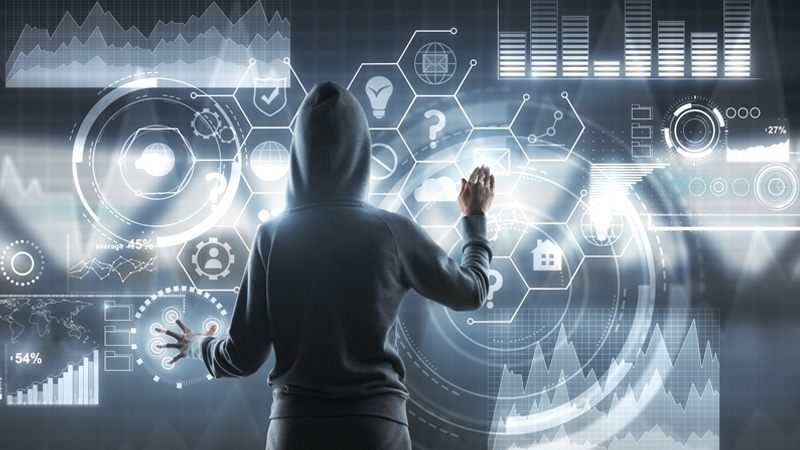 back view of a hacker in hoody pushing on digital sensor blockchain screne with icons and financial chart.